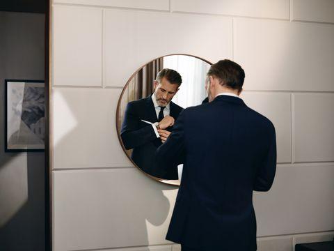 Formal wear, Event, Suit, Room, Photography, Gesture, White-collar worker, Interior design, Businessperson, Art,