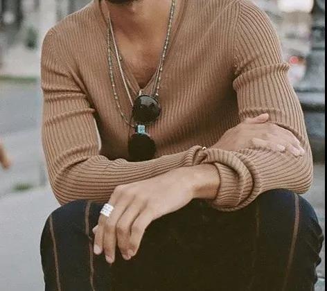 Sweater, Outerwear, Street fashion, Beige, Arm, Hand, Eyewear, Neck, Fashion accessory, Necklace,