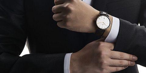 Suit, Formal wear, Tuxedo, Hand, Wrist, Gesture, Outerwear, Finger, Businessperson, White-collar worker,